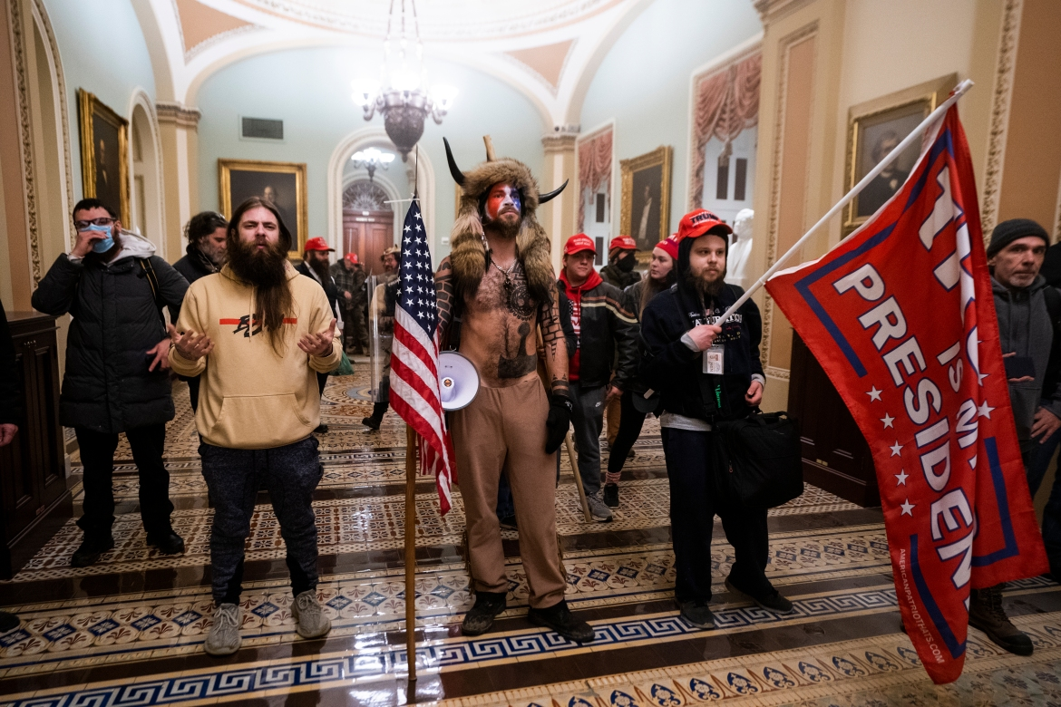 Supporters of US President Donald Trump stand by the door to the Senate chambers after they breached the US Capitol security in Washington [EFE/JIM LO SCALZO]