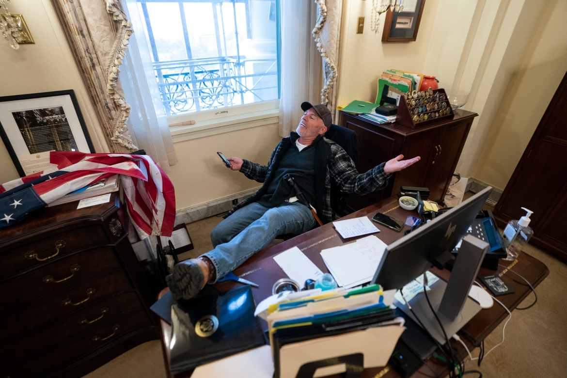 A supporter of US President Donald J Trump sits on the desk of US House Speaker Nancy Pelosi, after Trump-supporting rioters breached US Capitol security. [Jim Lo Scalzo/EPA]