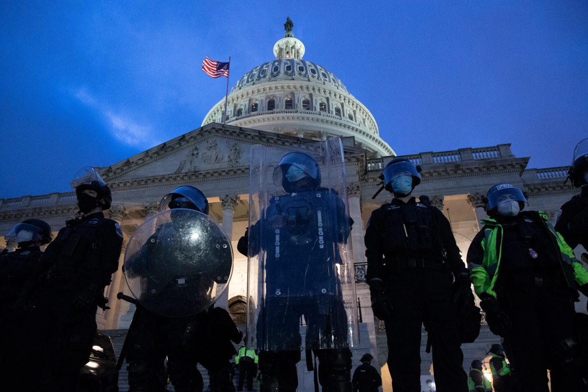 Police stand outside the East Front of the US Capitol at dusk as a curfew begins after pro-Trump protesters stormed the building. [Michael Reynolds/EPA]