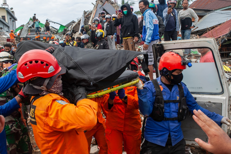 Anggota tim SAR Indonesia membawa jenazah korban ditarik dari reruntuhan bangunan yang rusak akibat gempa berkekuatan 6,2 skala Richter di Mamuju.  [Opan Bustan / EPA]