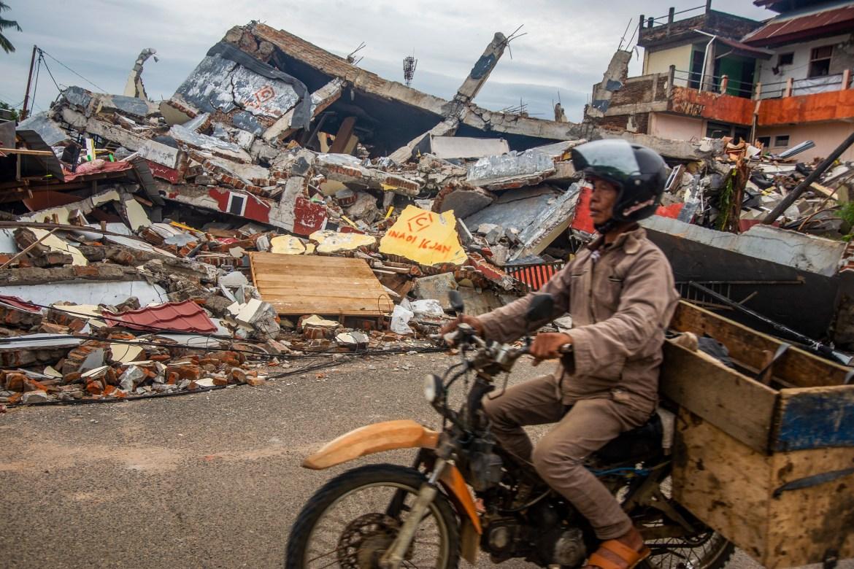 Seorang pria mengendarai sepeda motornya melewati rumah-rumah yang ambruk setelah gempa bumi di Mamuju, Sulawesi Barat.  [Iqbal Lubis / EPA]