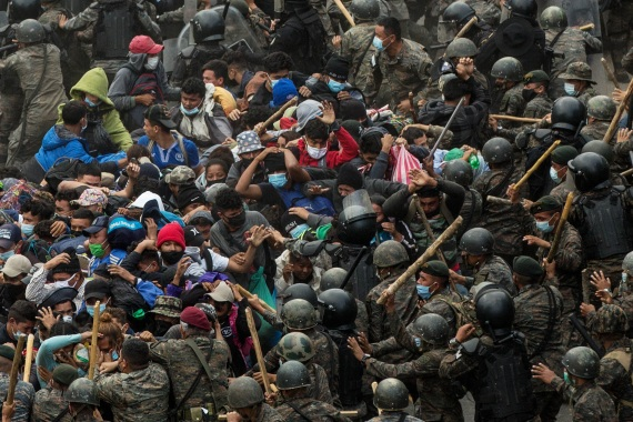 Guatemalan security forces surround the migrant caravan on a road near the border with Honduras. [Esteban Biba/EPA]