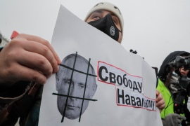 A protester holds a poster showing Russian President Vladimir Putin and reading 'Freedom for Navalny' during a protest in support of the Russian opposition leader in Moscow. [Maxim Shipenkov/EPA]