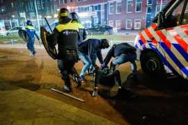 A man is arrested by police during clashes in Rotterdam on Monday. [Marco De Swart/EPA]