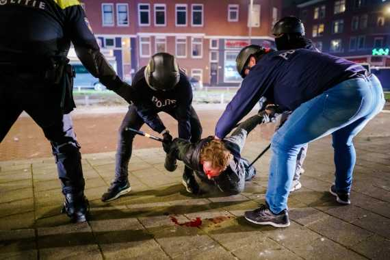 A man is arrested by police during violence in Rotterdam on Monday. [Marco De Swart/EPA]
