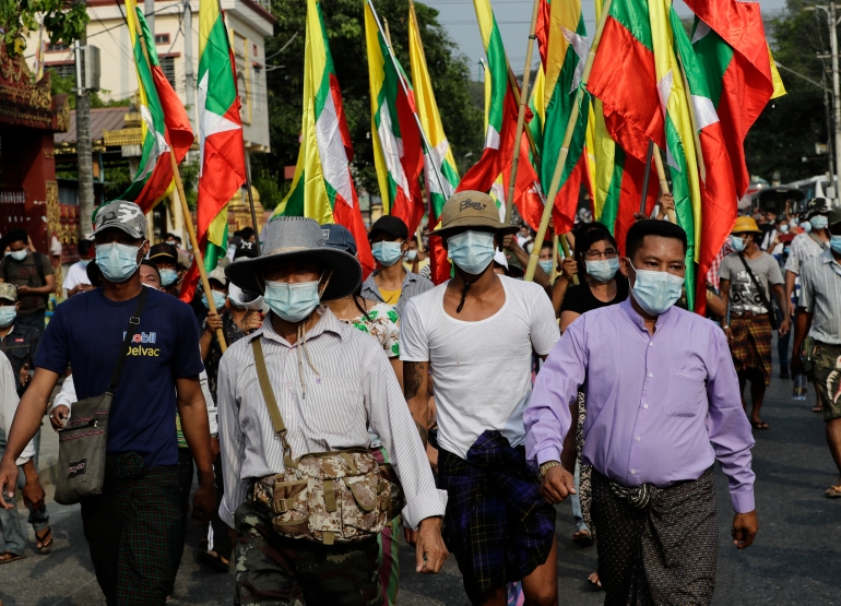 Military supporters holding the Myanmar national flags march in a protest against the election commission [Lynn Bo Bo/EPA]