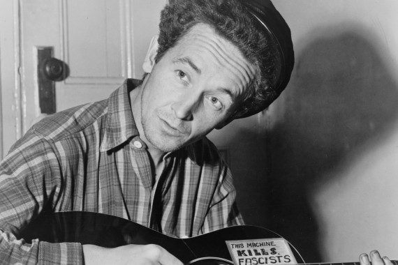 Woody Guthrie is seated playing a guitar that has a sticker attached reading: This Machine Kills Fascists [Library of Congress]