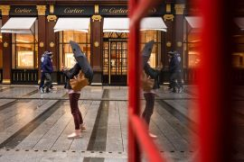 Pedestrians pass empty displays at a closed Cartier luxury watch and jewelry store in London, the United Kingdom, where the young and lowest paid have taken the hardest economic hit during the coronavirus crisis [File: Simon Dawson/Bloomberg]