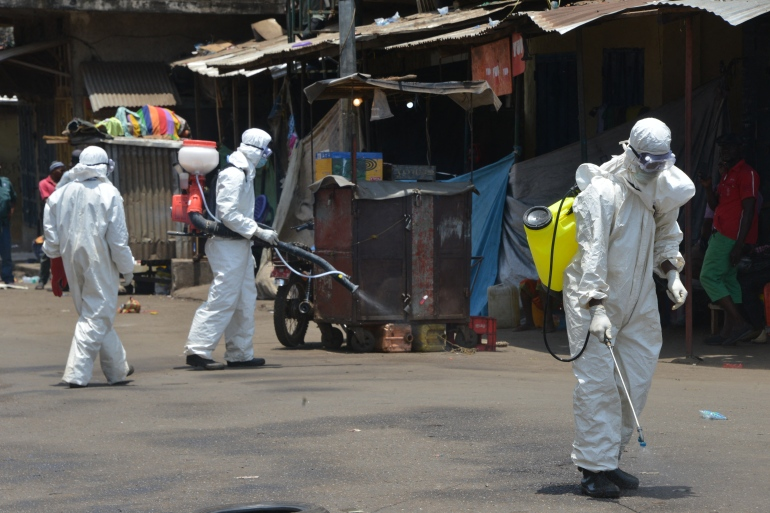 Workers dressed in full body gear disinfect shops and streets in Conakry, Guinea, on April 12, 2020 during a cleaning and disinfection campaign [Cellou Binani/AFP]