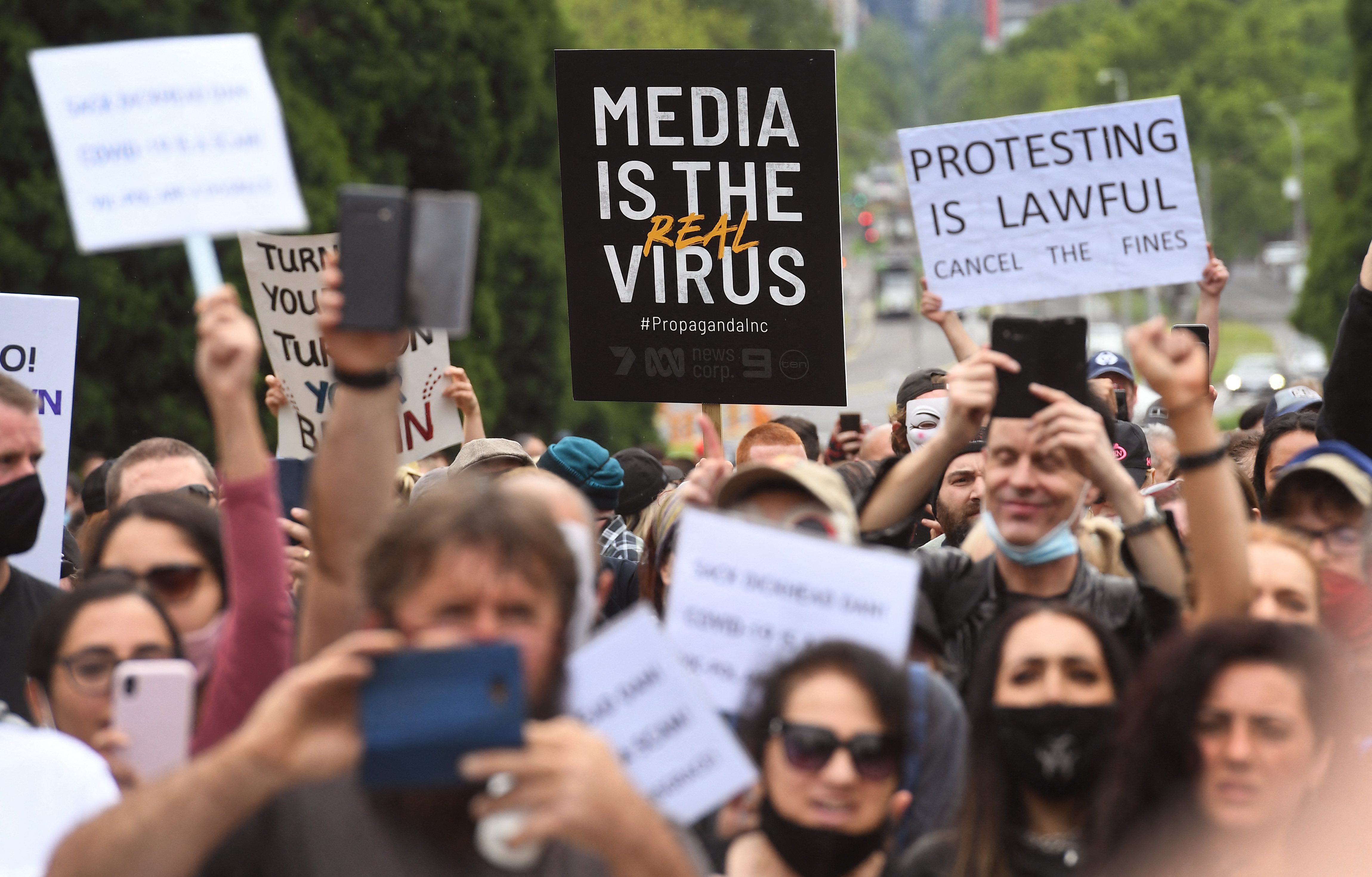 Protesters hold up placards during an anti-lockdown rally in Melbourne on October 23, 2020, amid the COVID-19 coronavirus pandemic [William West/AFP]