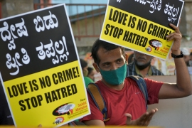 An activist holds placards during a demonstration condemning the decision of various BJP-led state governments to pass 'love jihad' laws, in Bangalore [File: Manjunath KiranAFP]