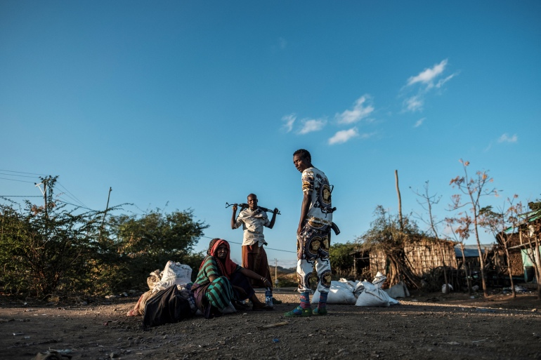 Men holding weapons stand next to a woman in the village of Bisober, in Ethiopia's Tigray region [File: AFP]
