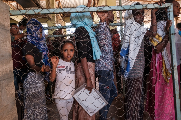 Eritrean refugees queue during a distribution of items organised by the UNHCR at Mai Aini Refugee camp, in Ethiopia, on January 30, [File: Eduardo Soteras/AFP]
