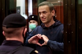 Navalny, pictured inside a glass cell during the court hearing in Moscow, was jailed for three and a half years although time he has already served under house arrest will reduce the term to two years and eight months [Handout/Moscow City Court press service via AFP]