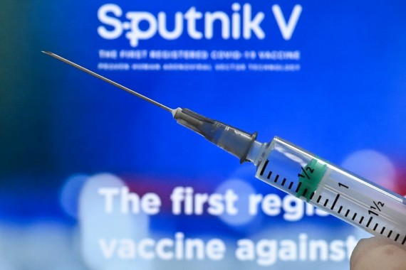An illustration picture shows a syringe with the webpage of Russia's Sputnik V vaccine [Kirill Kudryavtsev/AFP]