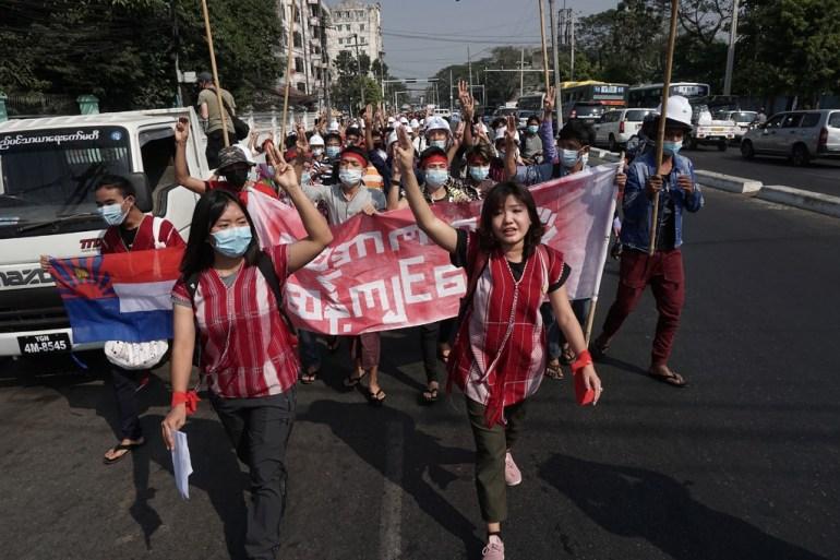 Para pengunjuk rasa memberikan hormat tiga jari selama demonstrasi menentang kudeta militer di Yangon pada hari Sabtu [Stringer / AFP]