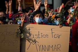 Protesters hold placards and flowers during a demonstration against the military coup in Yangon on February 7, 2021 [Ye Aung Thu/ AFP]
