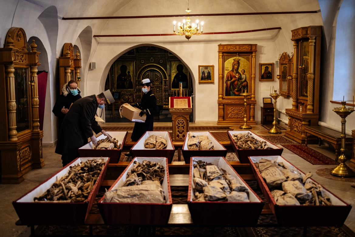French officials from the embassy in Moscow arrange remains of Russian and French soldiers who died during Napoleon's 1812 retreat, in communal coffins during a ceremony in a small church in the monastery of John the Precursor in the town of Vyazma. [Dimitar Dilkoff/AFP]