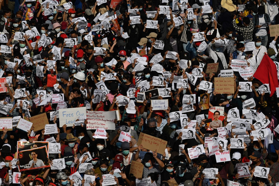 Protesters hold signs demanding the release of detained Myanmar leader Aung San Suu Kyi. [Sai Aung Main/AFP]