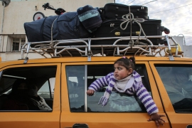 A girl looks on through the window of a vehicle while waiting at the Rafah border crossing's departure area to travel from the Gaza Strip into Egypt [Said Khatib/AFP]