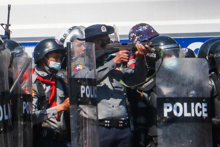Seorang petugas polisi (tengah) mengarahkan senjata selama bentrokan dengan pengunjuk rasa yang mengambil bagian dalam demonstrasi menentang kudeta militer di Naypyidaw pada hari Selasa [Stringer / AFP]