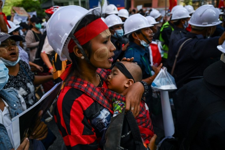 A protester carries a child as she marched with thousands of protesters in Yangon on Wednesday, as they continue to defy warnings by the coup leaders [Ye Aung Thu/AFP]