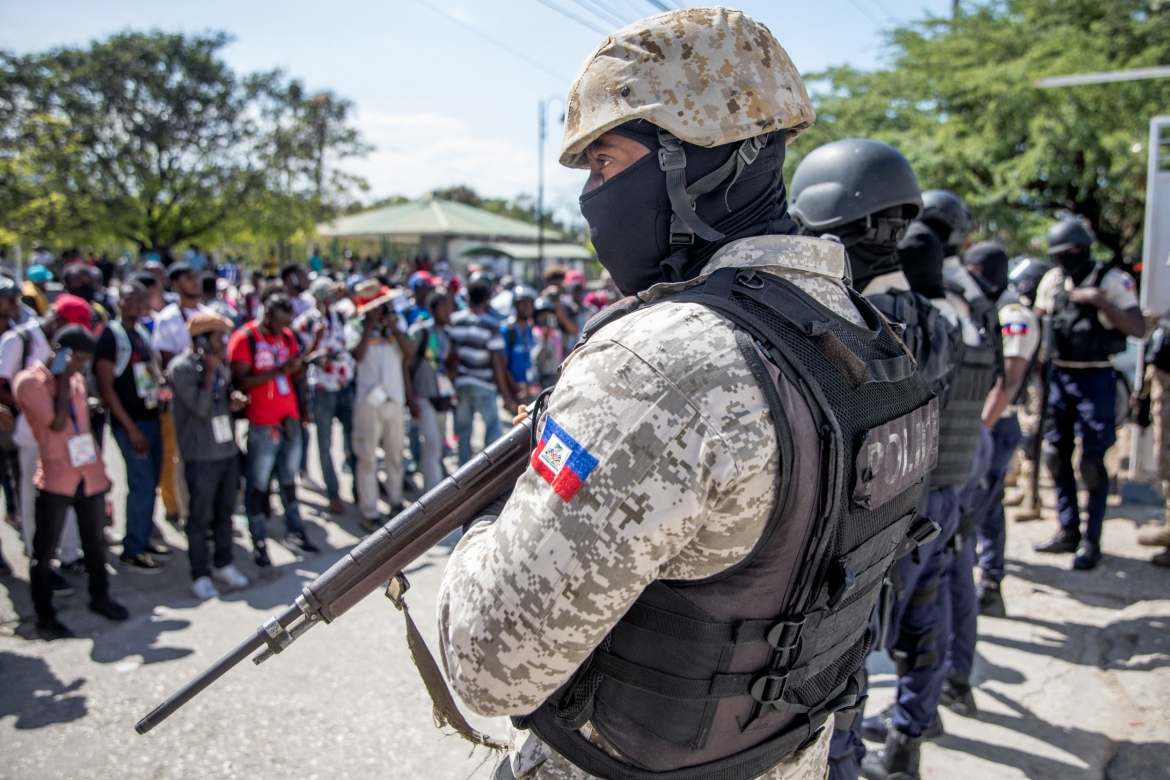 Journalists face armed police as they gather outside the Departmental Directorate of Police to file a complaint after they were targeted with tear gas while covering a protest against the Haitian president. [Valerie Baeriswyl/AFP]