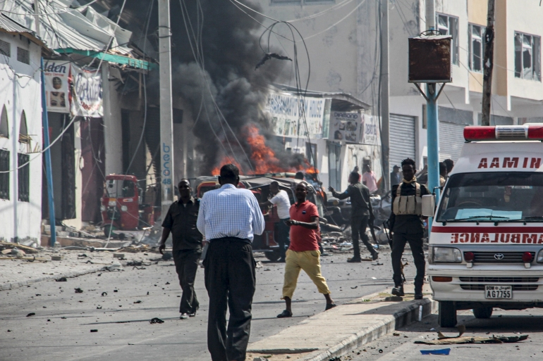 Somali security officers stand around the site of a car bomb explosion [Stringer/AFP]