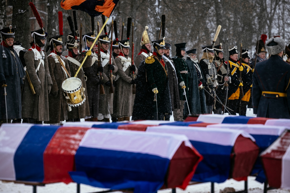 Re-enactors in period uniforms stand next to coffins containing remains of Russian and French soldiers during a burial ceremony in the western town of Vyazma. [Dimitar Dilkoff/AFP]