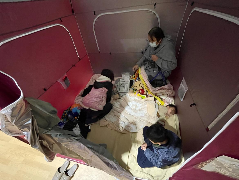 Sebuah keluarga yang dievakuasi beristirahat di tempat penampungan yang didirikan di arena olahraga di Soma.  [Jiji Press melalui AFP]