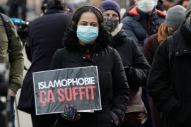 A woman holds a placard reading 'enough of Islamophobia' as protesters demonstrate against the 'anti-separatism' bill, in Paris on February 14, 2021 [Geoffroy Van Der Hasselt/AFP]