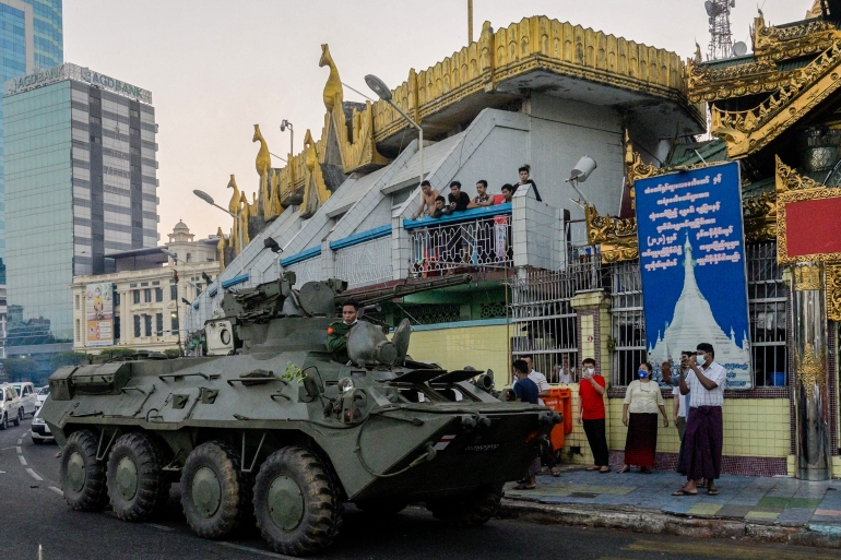 An armoured vehicle drives next to the Sule Pagoda, following days of mass protests against the military coup, in Yangon on February 14, 2021 [Thet Htoo/AFP]