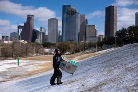 A boy walks up a snow-covered hill after sledding down it in a box, in Houston, Texas, the United States. [Mark Felix/AFP]