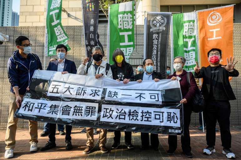 Hong Kong pro-democracy activists shout slogans in support of veteran activists outside the West Kowloon Magistrates Court in Hong Kong on February 16, 2021, as they go on trial for organising one of the biggest democracy protests to sweep the city in 2019 [Anthony Wallace/ AFP]