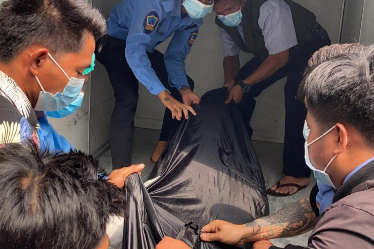 Hospital staff carry a body bag bearing the remains of Mya Thwate Thwate Khaing, who was shot in the head on February 9 during an anti-coup protest in Myanmar's capital Naypyidaw [Stringer/AFP]