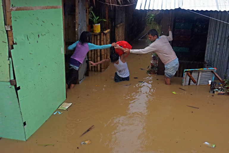 Residents help a neighbour carrying belongings wade through their flooded houses due to heavy rain brought by Tropical Storm Dujuan in Tandag City, Surigao del Sur province, on Mindanao island on February 21, 2021 [Erwin Mascarinas/AFP]