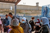Palestinians wait to receive the Pfizer-BioNTech COVID-19 vaccine provided by Israel's Magen David Adom medical services at Qalandiya checkpoint on the crossing between the occupied West Bank city of Ramallah and occupied East Jerusalem, on February 23, 2021 [Ahmad Gharabli/ AFP]