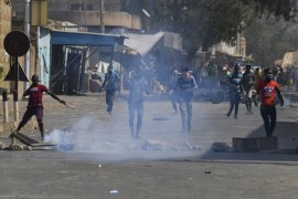 Niger's opposition demonstrators throw stones during clashes with police [Issouf Sanogo/AFP]
