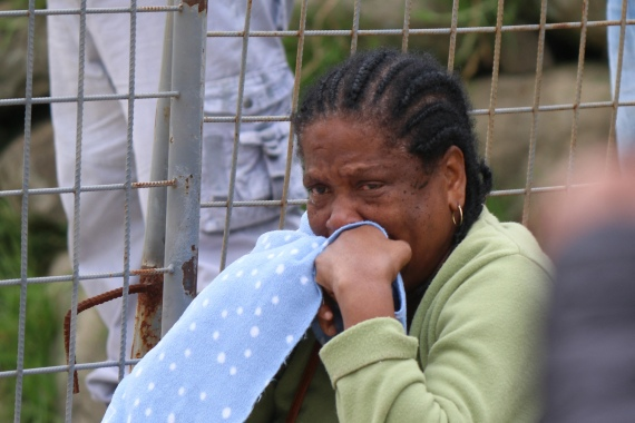 A relative of a deceased prisoner cries outside the Zone 6 Forensic Centre. [Fernando Machado/AFP