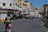 A policeman holds a stop sign in an almost deserted avenue in the Jordanian capital Amman, during a coronavirus lockdown [Khalil Mazraawi/AFP]