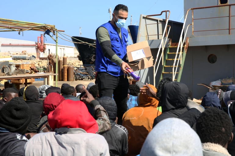 Rescued migrants receive snacks as they sit aboard a Libyan coastguard vessel arriving at the capital Tripoli's naval base on February 28, 2021 [Mahmud Turkia/AFP]
