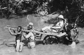 A file photo taken in Senegal, then a French colony, in the 1930s shows a European being carried through a river by African porters in a sedan chair [File: AFP]