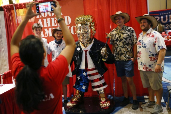 People take a picture with a gold statue of former US President Donald Trump's statue on display at the Conservative Political Action Conference [Joe Raedle/Getty Images/AFP]
