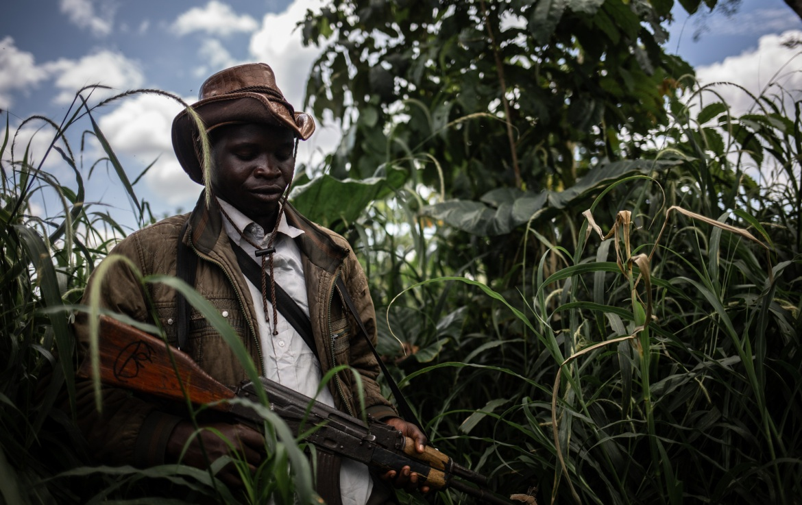 A man from a CODECO sub-group walks through the bush during a reconnaissance patrol. In August, President Felix Tshisekedi sent a delegation of former rebel leaders to Ituri to negotiate peace with CODECO. These discussions have resulted in the signing of a unilateral commitment from armed groups to cease hostilities and engage in a negotiation process with the government. The conflict risks escalating further in the near future if a long-term solution to the Ituri crisis is not found to break the cycle of violence and allow hundreds of thousands of displaced people to return home. Dialogue between communities to resolve disputes over land will be key in the resolution of the conflict and the appeasement of the region. [Tom Peyre-Costa/NRC]