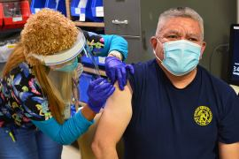 US Public Health Service Captain Jefferson Fredy, a member of the Navajo Nation and the chief of pharmacy at the Crownpoint Service Unit, receives a COVID-19 vaccine at the Crownpoint Healthcare Facility in the Navajo Area IHS on December 14, 2020 [Courtesy of IHS]