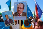 Women carry posters with the image of the newly elected Somalian President Mohamed Abdullahi Mohamed as they celebrate his victory, near the Daljirka Dahson monument in Mogadishu, Somalia February 11, 2017. REUTERS/Feisal Omar