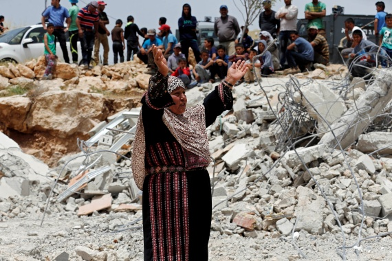A woman reacts in front of a Palestinian house demolished by Israeli forces near Hebron [File: Mussa Qawasma/Reuters]