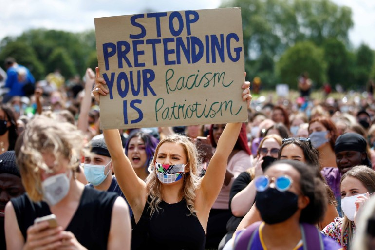 A demonstrator holds a placard as she attends a Black Lives Matter protest at Hyde Park, following the death of American citizen George Floyd in Minneapolis police custody, in London, Britain on June 20, 2020 [File: Reuters/Henry Nicholls]