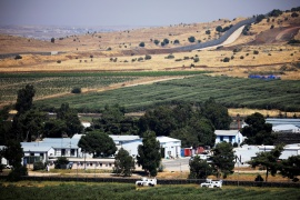 UN vehicles drive near the Israel-Syria frontier seen from the Israeli-occupied Golan Heights [File: Amir Cohen/Reuters]