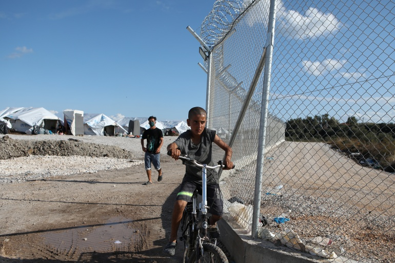 A boy rides a bike next to the fence of the Kara Tepe camp for refugees and migrants on the island of Lesbos, Greece, in October 2020 [File: Elias Marcou/Reuters]